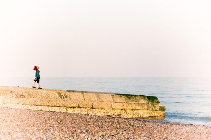 Boy in jester hat on the beach wall