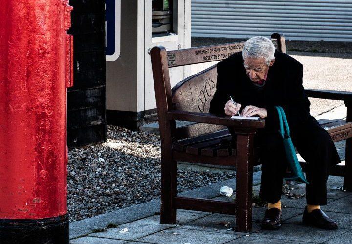 man writing postcard the stade hastings