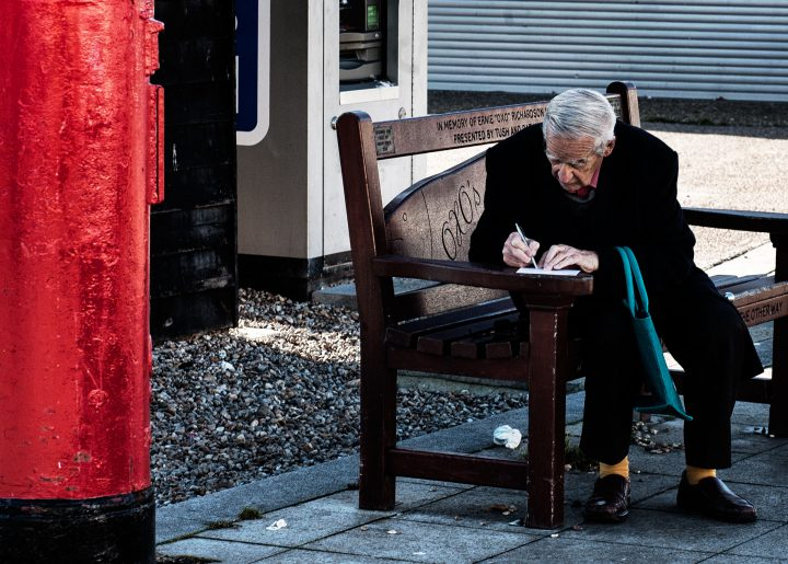 man writing postcard the stade hastings